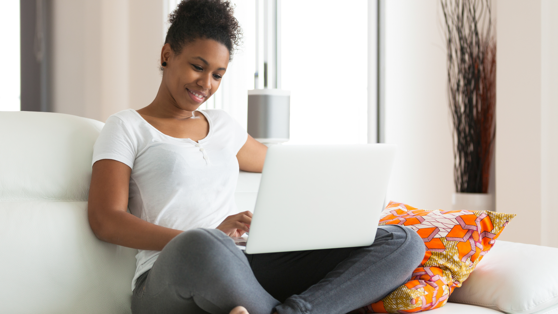 Girl on sofa on her laptop at home